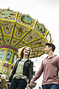 Teenage couple at fun fair with chairoplane in the background - UUF000663