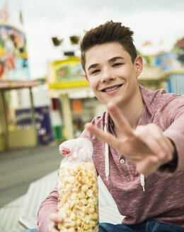 Portrait of happy teenage boy with popcorn showing victory-sign at fun fair - UUF000661