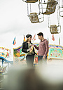 Portrait of teenage couple with popcorn at fun fair - UUF000634