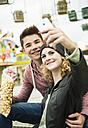 Teenage couple with popcorn photographing themself at fun fair - UUF000632