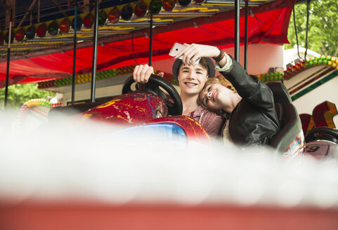 Teenage couple sitting in bumper car photographing themself with smartphone - UUF000649