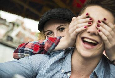 Teenage girl covering eyes of her boyfriend with her hands - UUF000646