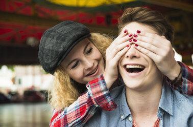 Teenage girl covering eyes of her boyfriend with her hands - UUF000669