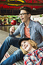 Portrait of happy teenage couple with candied apple at fun fair - UUF000670
