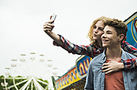 Portrait of teenage couple photographing themself at fun fair - UUF000671