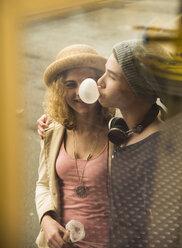 Teenage girl watching gum bubble of her boyfriend - UUF000623