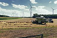 Germany, North Rhine-Westphalia, Sassenberg, Harvester in field, wind wheels in background - MEM000039