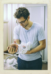 Father holding his newborn baby in hospital room - MFF001096