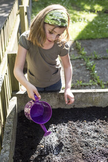 Portrait of girl pouring seeds in raised bed - STB000179
