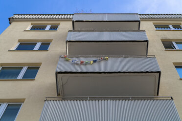 Facade with balconies of multi-family house, view from below - TCF004081