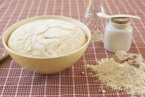 Bowl of raw yeast dough and ingredients of yeast dough on cloth - SABF000014