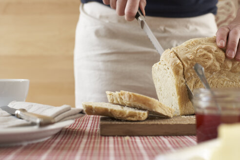 Woman cutting home-made yeast bread on chopping board, partial view - SABF000020
