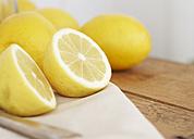 Sliced and whole lemons, knife and cloth on wood - SABF000031