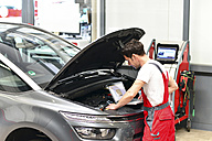Car mechanic in a workshop using modern diagnostic equipment - LYF000027