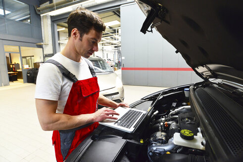 Car mechanic in a workshop using modern diagnostic equipment - LYF000028