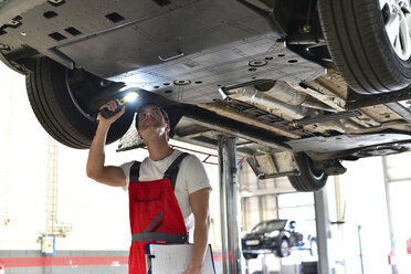 Car mechanic in a workshop checking underbody of a car - LYF000032