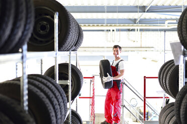 Car mechanic at shelf with tires - LYF000035