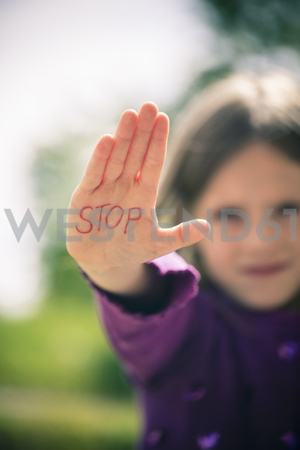 Little girl showing palm with the word STOP on it - SARF000642