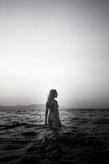 Naked young woman walking in the sea by twilight - AJF000037