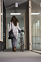 Business woman leaving office with racing cycle - FKF000499