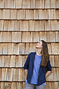 Creative business woman standing in front of wood shingle panelling - FKF000508