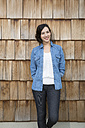 Portrait of young creative business woman in front of wood shingle panelling - FKF000513