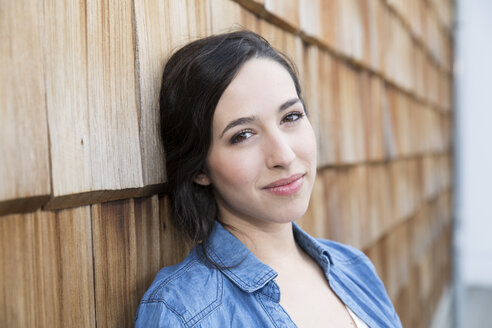 Portrait of young creative business woman in front of wood shingle panelling - FKF000516