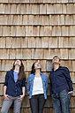 Group picture of three creative business people in front of wood shingle panelling - FKF000519