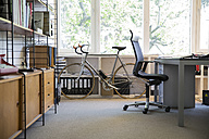Racing cycle standing at workplace of modern office - FKF000522