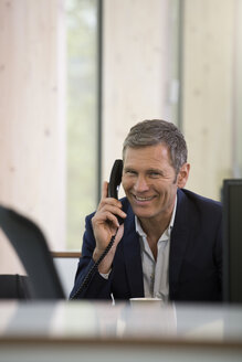 Portrait of smiling business man telephoning at workplace - FKF000555
