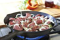 Preparing beef goulash in frying pan on gas stove - SRSF000495