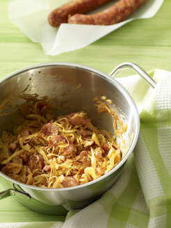 Pot of sauerkraut with slices of sausages, kitchen towel and two sausages on parchment paper - SRS000499