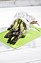 Bunch of green asparagus in white paper bag lying on green chopping board and white wood - MAEF008339
