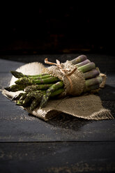 Bunch of green asparagus on jute and dark wood - MAEF008343