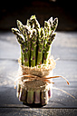Bunch of green asparagus standing on dark wood - MAEF008345