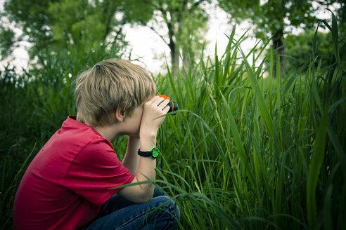 Little boy sitting on meadow watching something with binocular - SARF000660