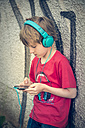 Portrait of boy with smartphone and headphones in front of facade - SARF000664