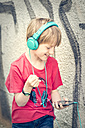 Portrait of happy boy with smartphone and headphones in front of facade - SARF000665