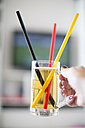 Woman's hand holding beer mug with three drinking straws in German national colours - SARF000684