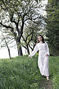 Young woman wearing white dress walking on footpath - VTF000256