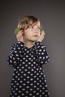 Portrait of little girl holding broccoli on his ears - OJF000023