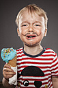 Portrait of crying looking little boy with painted beard and ice cream - OJF000028