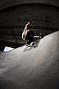 Skateboarder performing trick at skateboard park - KJ000299