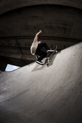 Skateboarder performing trick at skateboard park - KJ000299