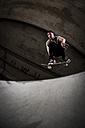 Skateboarder jumping in the air at skateboard park - KJ000302