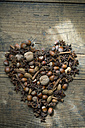 Heart shaped of star anise, nuts and cinnamon sticks on wood - ASF005406