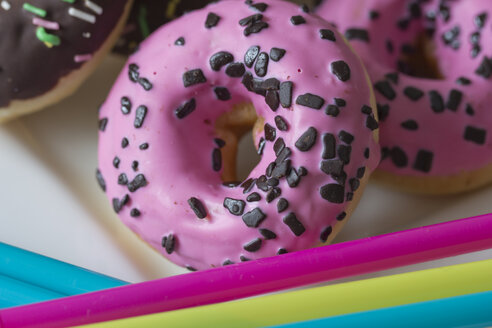 Plate of pink doughnuts decorated with chocolate granules, close-up - YFF000148