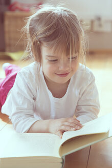 Portrait of smiling little girl with book - LVF001346