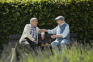 Two old friends sitting on park bench playing chess - UUF000737