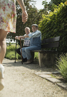 Two old men sitting on park bench watching legs of passing woman - UUF000742
